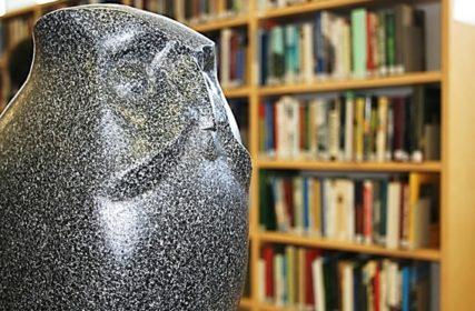 Pöllö-patsas takana kirjahyllyä