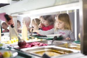 Lapsia ruokalinjastolla ottamassa ruokaa.