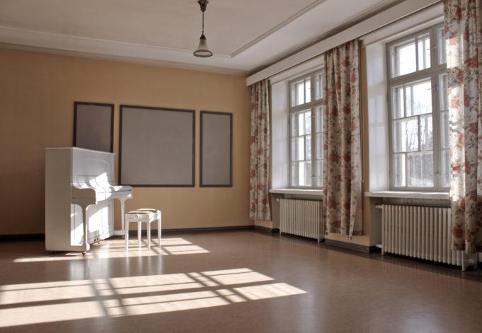 Kauniissa Balettisalissa on valkoinen piano ja ruusukuvioiset verhot.