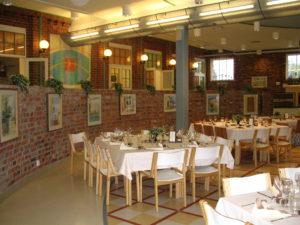 Hempankaaren juhlatilassa on tauluja punatiilisillä seinillä.