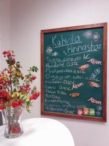 Maljakossa syksyn väreissä olevia viherkasveja ja seinällä liitutaulu, jossa kahvilan hinnasto.