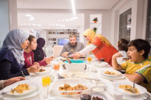 Ulkomaalainen perhe yhdessä aterialla.