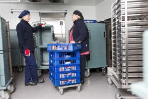 Kaksi ruokapalveluiden työntekijää täyttämässä ruokien kuljetukseen käytettäviä lämpövaunuja.