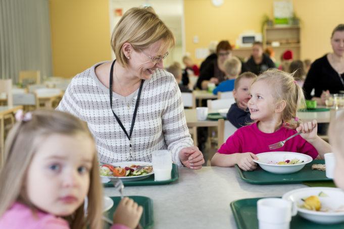 Päiväkodin opetusruokailu tilanne. Aikuinen ruokailee lasten kanssa. Aikuinen ja lapsi katsovat toisiaan ja hymyilevät.