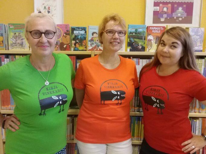 Kirjaston kirjavinkkarit poseeraavat kirjahyllyn edessä pukeutuneina Kirjavinkkari-paitoihin.