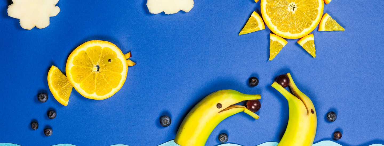 Ruokataidetta. Sinisellä pohjalla kaksi päästään halkaistua banaania. Koristeltu viinirypäleillä. Näyttävät leikkisiltä delffiineiltä. Lisäksi kaksi sitruunan siivua, joista on tehty kala ja aurinko.