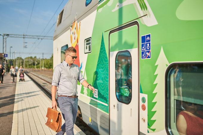 Mies nousee vihreä-valkoisen Intercity-junan kyytiin Nokian asemalaiturilla. Laiturilla on myös muita matkustajia lastenrattaineen.