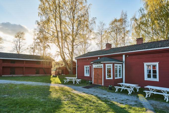 Hinttalan kotiseututalo ja etualalla nurmikkoa. Aurinko paistaa ja on kesäistä.
