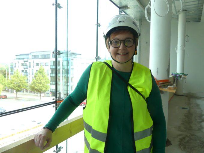 Arja Laitinen kuvattuna kirjaston kolmannessa kerroksessa.