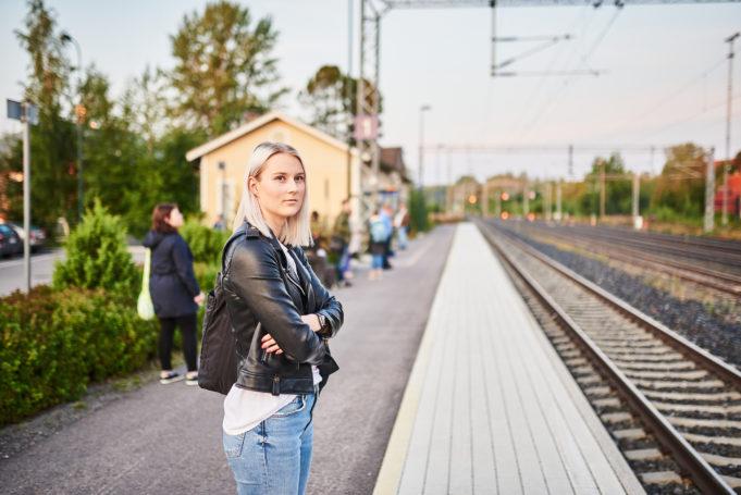 Nuori nainen seisoo Nokian rautatieaseman laiturilla ja odottaa junaa.