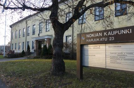 Nokian keltainen kaupungintalo, edustalla Nokian kaupungin kyltti ja lehdetön puu.