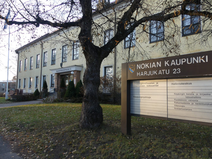 Nokian keltainen kaupungintalo, edustalla Nokian kaupungin kyltti ja puu.
