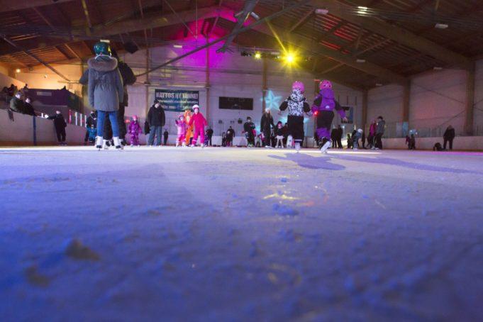 Loppiaistapahtumassa lapset luistelevat musiikin tahdissa tunnelmavalaistulla jäällä Nokian jäähallissa.