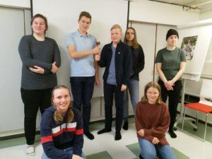 Nuorisovalstuuston jäsenet yhteiskuvassa. Kuvassa seitsemän nuorta, joista viisi seisoo takana ja kaksi kyykyssä edessä. Puheenjohtajat seisovat keskellä takana ja pitävät yhteisesti käsissä nuijaa.