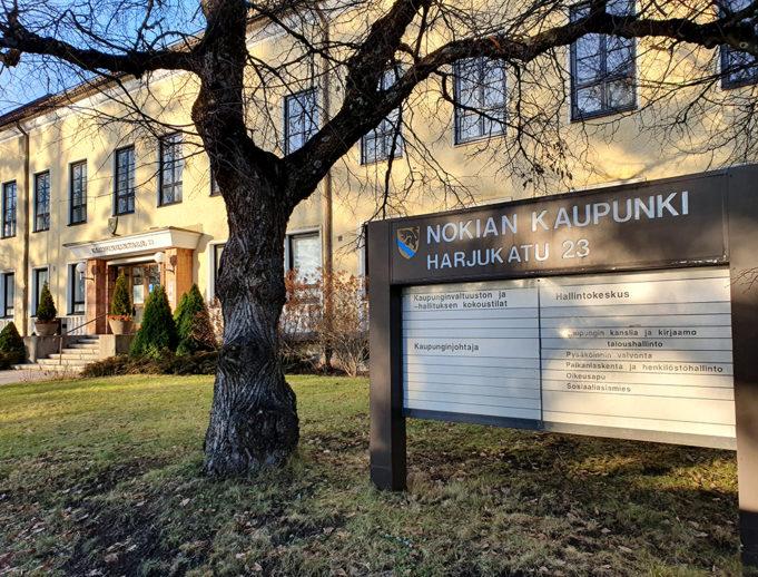 Nokian kaupungin kaupungintalo Harjukadulla. Kaupungintalo on keltainen vanha kivitalo, jonka edessä vihertää keväinen nurmikko ja nurmikolla on opastetaulu kaupungin toiminnoista, joita tarjotaan kaupungintalossa ja viereisessä virastotalossa.