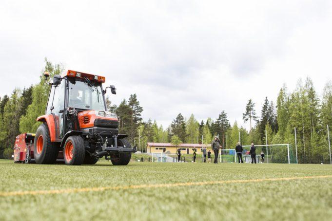Traktori-ruohonleikkuri ajaa jalkapallokentän nurmea.
