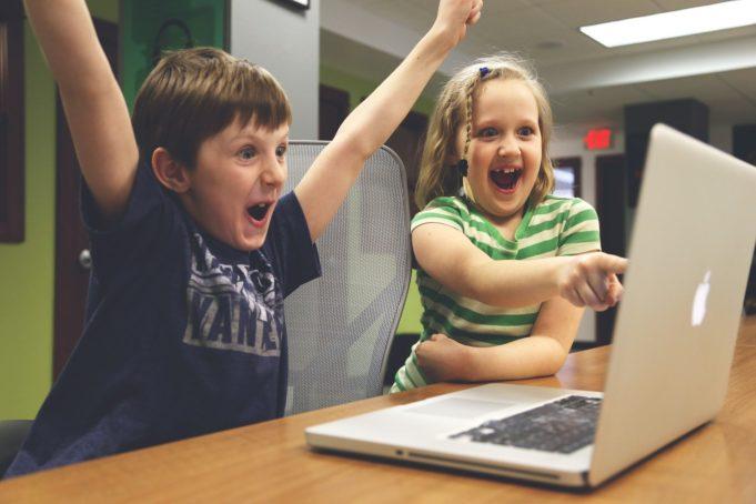 Kaksi innostunutta lasta istuu läppärin ääressä. Tyttö osoittaa näyttöä ja poika tuulettaa kädet ilmassa.