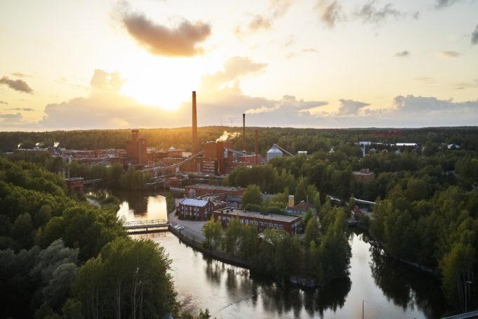 Nokian Tehdassaari kesäisenä aamuna auringon noustessa. Tehdassaaressa on vanhoja punatiilisiä rakennuksia ja edelleen toimivia tehtaita piippuineen.