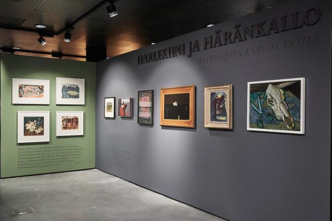 Näkymä ovelta Harlekiini ja häränkallo -näyttelyyn. Harmaalla ja vihreällä seinällä.