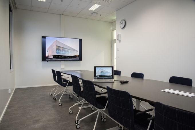 Kokoustila Fransissa on iso led-näyttö, iso yhteinen pöytä ja sen ympärillä tuolit kahdelletoistahenkilölle.
