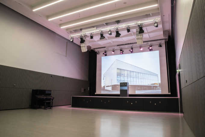 Korkeassa Hiomo-salissa on nostetettava esiintymislava, projektori ja värivalaistus.