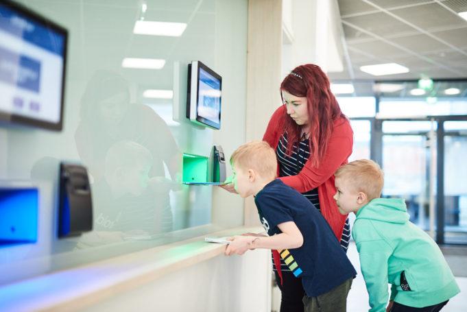 Kirjastonhoitaja näyttää innostuneille lapsille palautusautomaatin käyttöä. Mihin ne kirjat oikein katoavat?