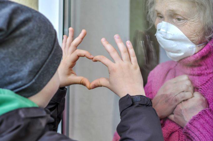 Nuori poika näyttää sormilla tehtyä sydäntä isoäidilleen, joka katsoo lasi-ikkunan takaa hengityssuojain kasvoillaan.