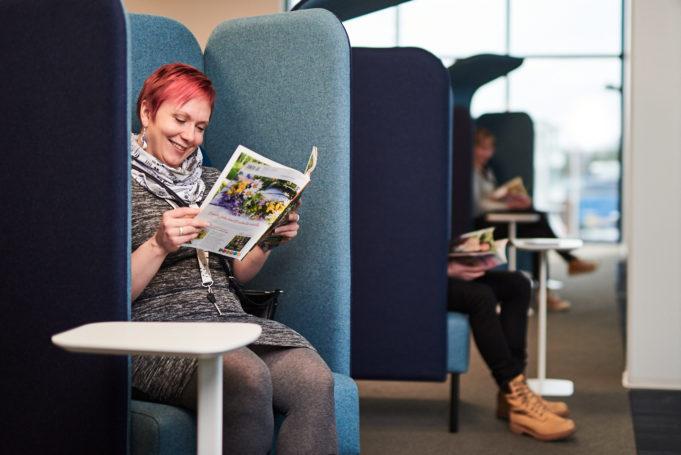 Asiakkaat lukevat lehtiä mukavissa nojatuoleissa.