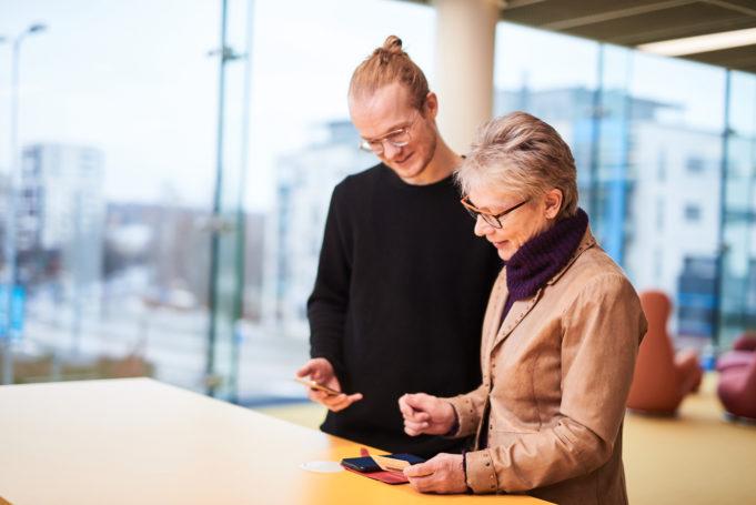 Informaatikko esittelee asiakkaalle henkilökohtaisesti mobiilikirjastosovellusta.