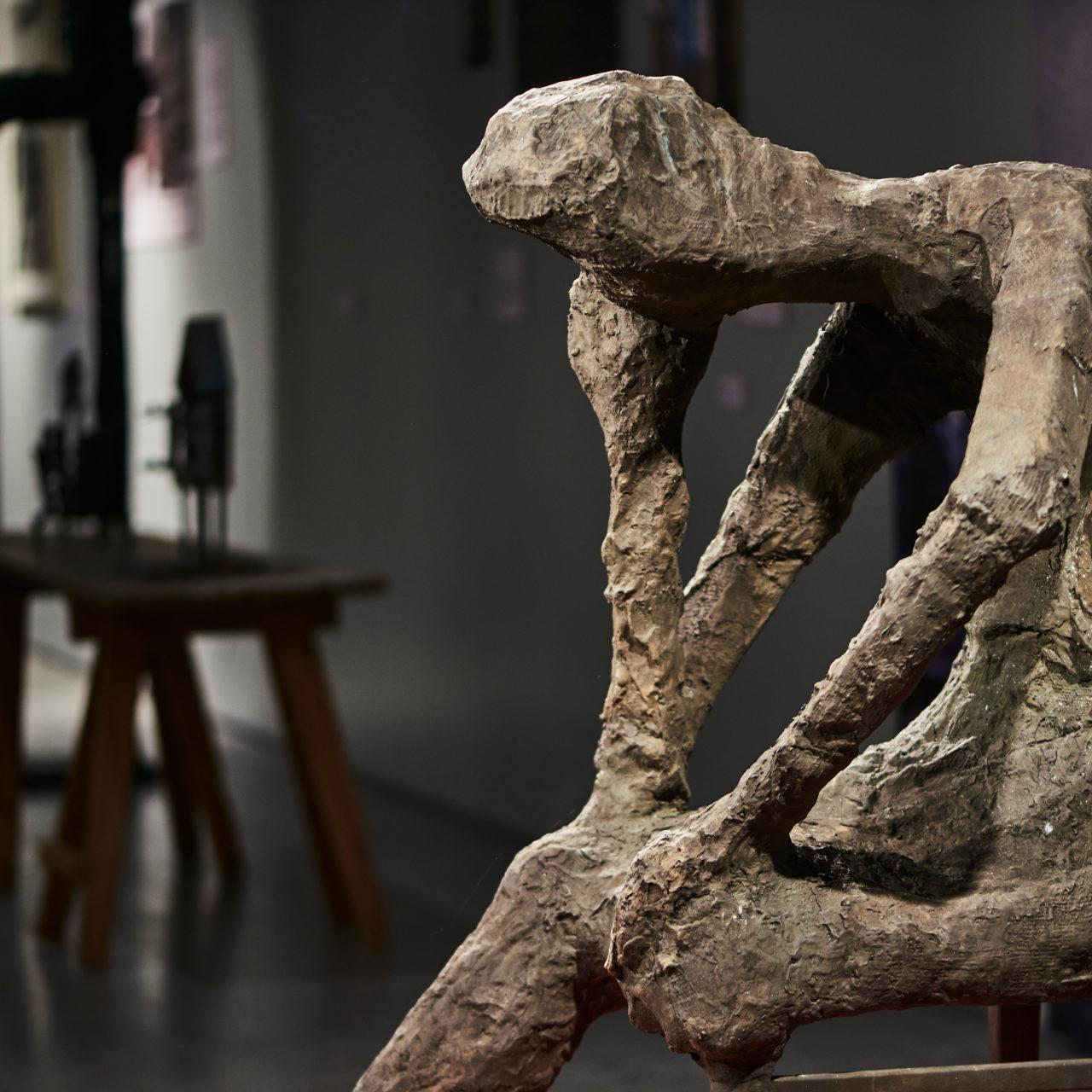 Ossi Somman näyttelyn nimikkoteos Näinkö tässä kävikin on kookas spronssiveistos, jossa ihmishahmo istuu etukumarassa käteensä nojaten.