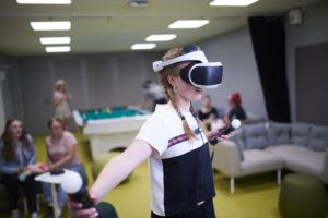 Nuori pelaa konsolipeliä VR- laseilla nuorisotila Nuksussa. Taustalla muita nuoria istumassa sohvilla ja pelaamassa biljardia.