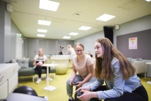 Nuorisotila Nuksussa kaksi nuorta pelaa etualalla konsolipeliä. Taustalla nuoria pelaa biljardia ja istuu sohvalla.
