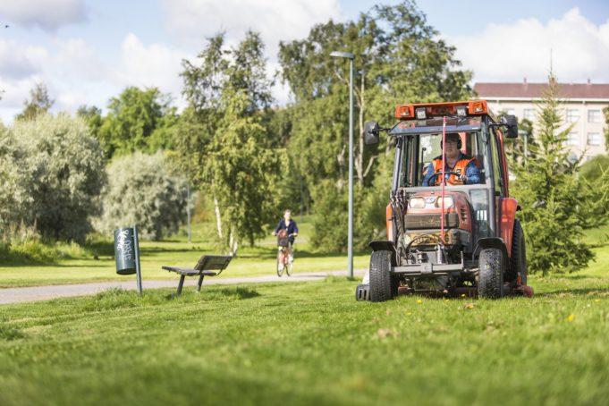Infrapalveluiden työntekijä leikkaa nurmikkoa pienellä traktorilla kesällä puistossa.