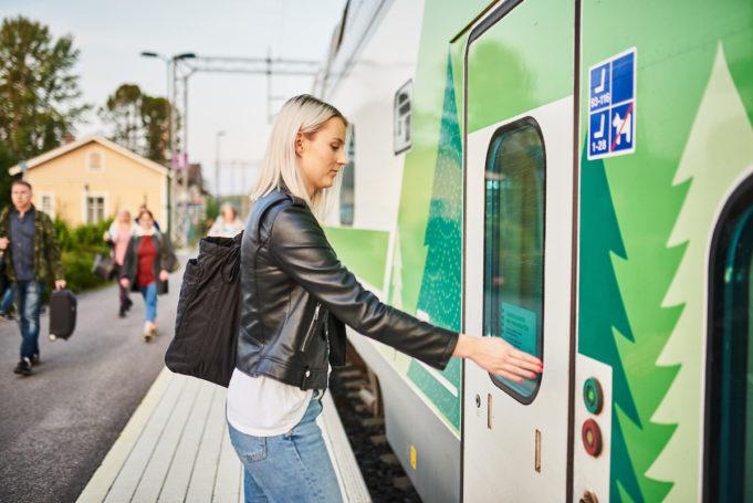 Nuori nainen nousee junan kyytiin Nokian asemalaiturilta. Hän painaa junavaunun ovessa olevaa avauspainiketta.