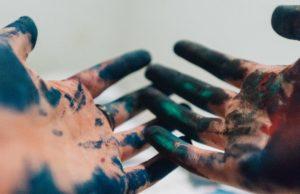 kädet, jotka sotkeentunut maalausväristä