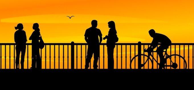 Ihmiset pyöräilevät ja seisoskelevat sillalla ihastelemassa auringonlaskua.