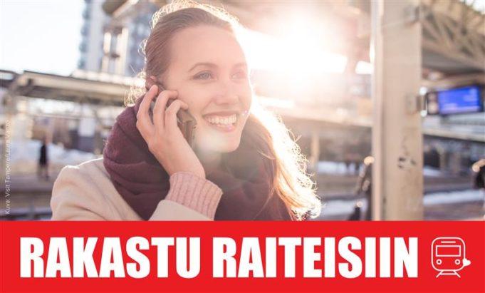Nainen puhuu matkapuhelimeen rautatieasemalla. Kuvan alla Rakastu raiteisiin -kampanjan tunnus, jossa Rakastu raiteisiin -teksti ja veturin kuva.
