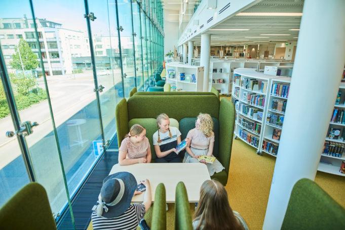 tytöt istuvat lukunurkkauksessa kirjastolla kesäaikaan.