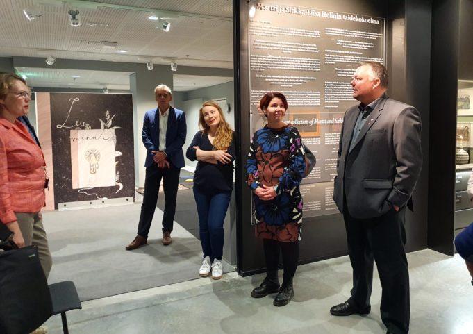 Kansanedustajat tutustuvat kirjasto- ja kulttuuritalo Virran taidenäyttelyyn. Kirjastopalvelupäällikkö Jarna Hara esittelee taidetila Romua.