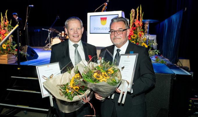 Harri Kallio (vas.) ja Sakari Ermala Pirkan päivän juhlassa kädessään kukkakimput ja kunniakirjat.