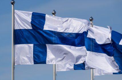 Kolme Suomen lippua liehuu tuulessa