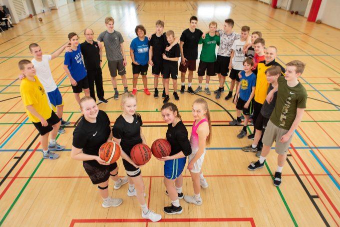 Iloisia koripalloilevia urheiluluokkalaisia aamutreeneissä Nokian lukion liikuntasalissa