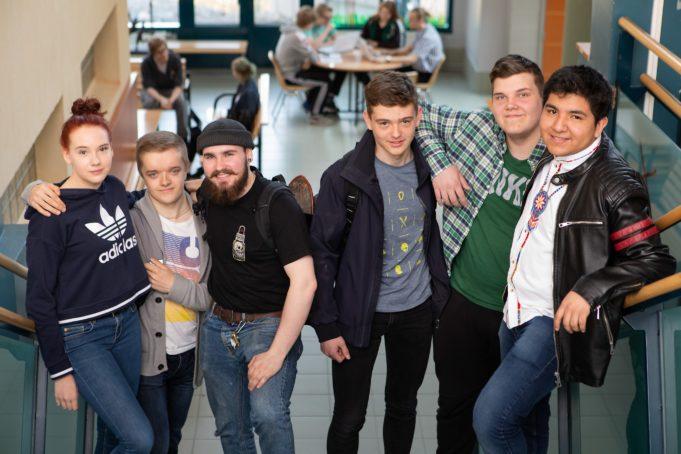 Kuusi hymyilevää lukiolaista Nokian lukion aulassa kädet toistensa harteilla.