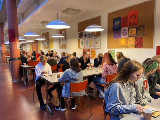 Oppilaita istuu ruokalassa syömässä glögiä ja leivoksia.