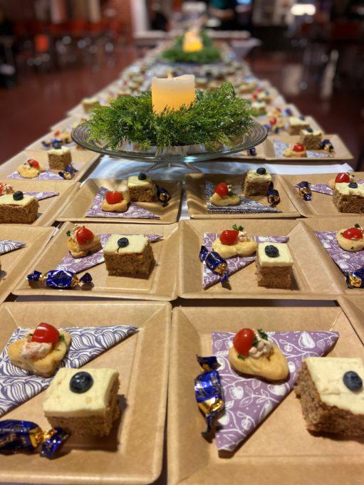 Pöydälle on katettuna kynttiläasetelmia ja nelikulmaisia lautasia. Jokaisella lautasella on lautasliina pieni leivos, cocktailpala ja suklaamakeinen.