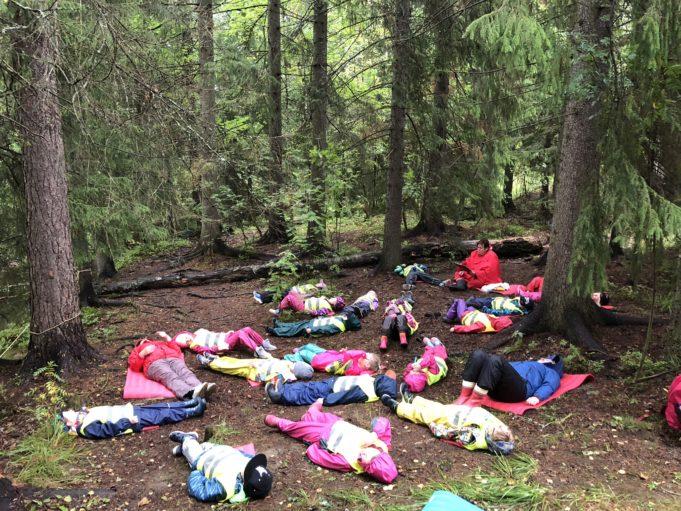 Alhoniityn päiväkodin lapset makaavat metsän keskellä maassa luontorentoutushetkessä.