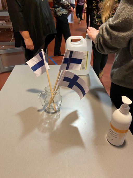 Paperisia Suomen lippuja ja käsidesipulloja pöydällä