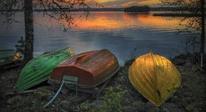 Kuvassa on Raine Lehtorannan kuvaamia värikkäitä soutuveneitä Pyhäjärven rannalla auringonlaskun aikaan