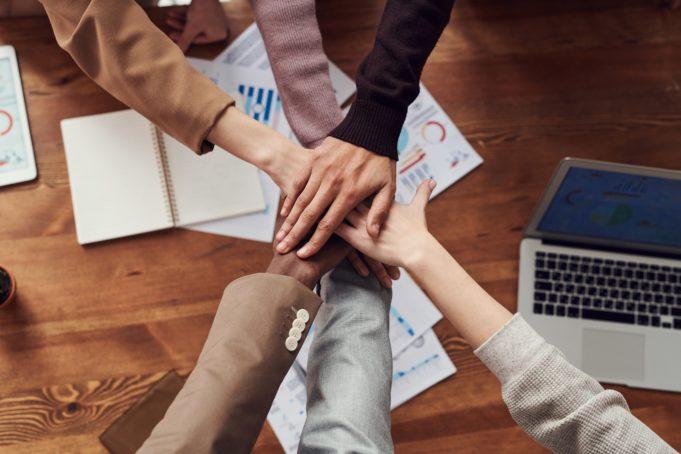Kuusi ihmistä on yhdistänyt kätensä yhteistyön merkiksi.