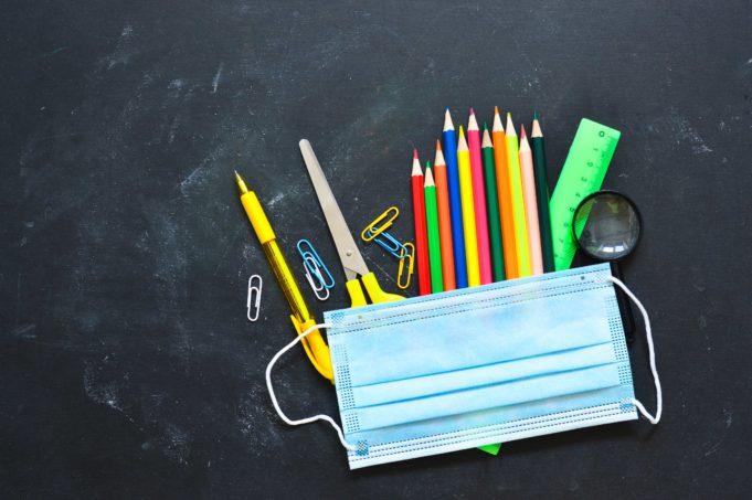 Liitutaulun päälle on aseteltu kasvomaski sekä värikyniä ja muita koulutarvikkeita.